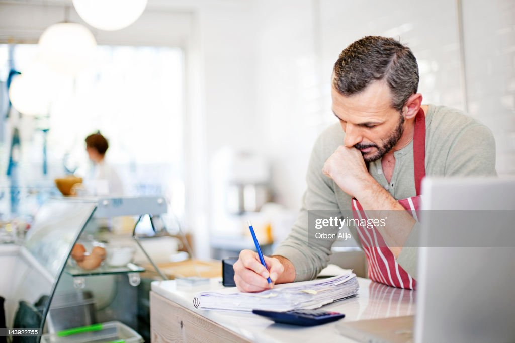 Business owner calculating : Stockfoto