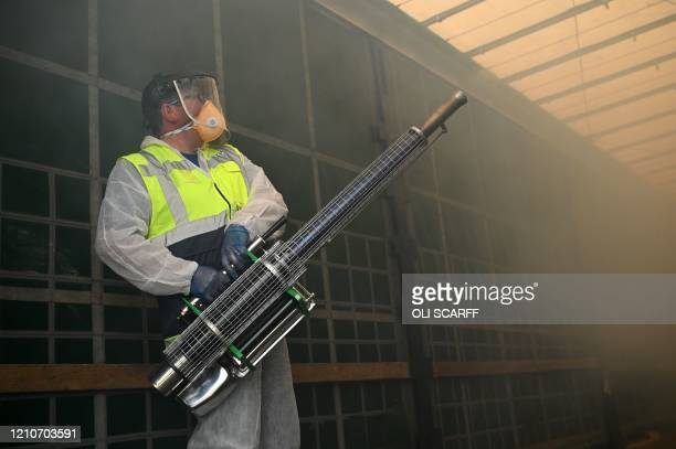 Business owner Chris Johnson uses a thermal fogger inside a lorry as he disinfect trucks at a haulage firm in Barnsley south Yorkshire on April 22...