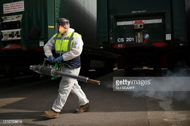 Business owner Chris Johnson uses a thermal fogger to disinfect trucks at a haulage firm in Barnsley south Yorkshire on April 22 during the...