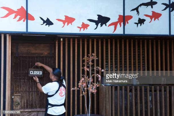 business owner hanging a closing sign on the door before opening the store - kanagawa prefecture stock pictures, royalty-free photos & images