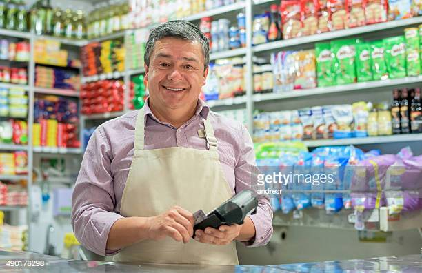 business owner holding a credit card reader - happy merchant stock pictures, royalty-free photos & images