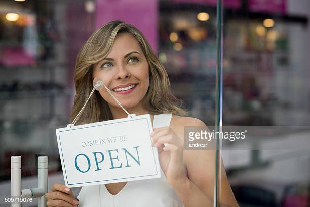 Business owner holding an open sign at a store