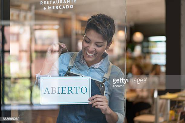 business owner holding an open sign in spanish - emprendedor fotografías e imágenes de stock
