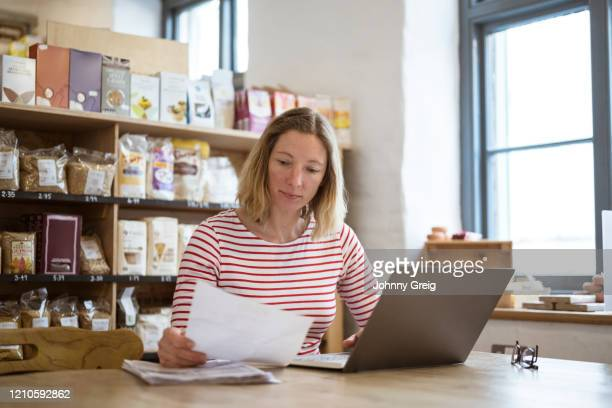 business owner in early 40s doing paperwork in her shop - femalefocuscollection stock pictures, royalty-free photos & images