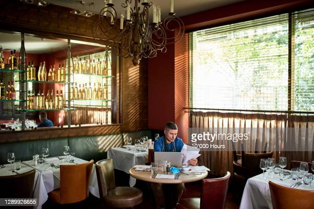 business owner in restaurant checking paperwork during covid - finance and economy stock pictures, royalty-free photos & images