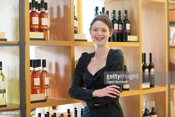 business owner in wine shop arms crossed looking at camera smiling - sigrid gombert stockfoto's en -beelden