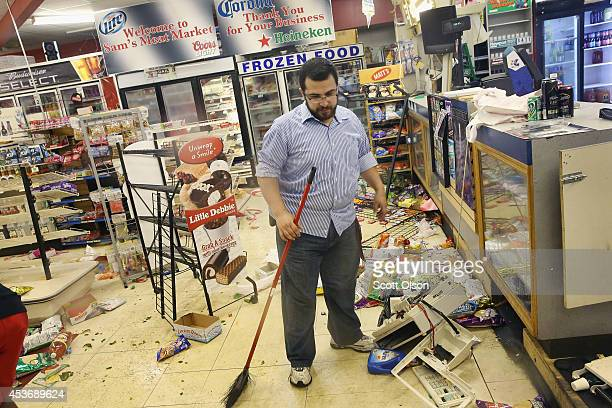 Business owner Mustafa Alshalabi cleans damage to his store, Sam's Meat Market, after it was looted during another night of rioting following...