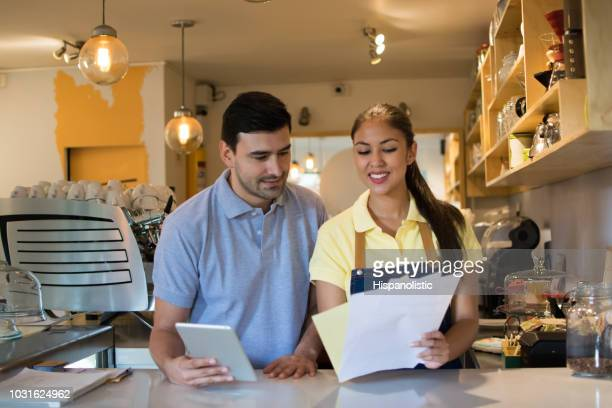 business owner of a coffee shop and waitress standing behind the counter - concepts & topics stock pictures, royalty-free photos & images
