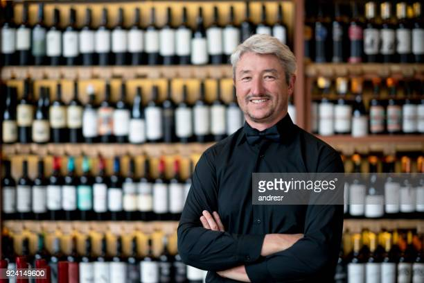 Business owner of a wine store looking at camera smiling with arms crossed