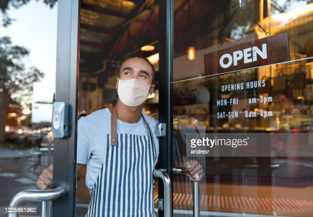 business owner opening the door at a cafe wearing a facemask - opening event stock pictures, royalty-free photos & images