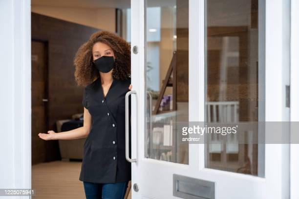business owner opening the door of her spa wearing a facemask - reopening stock pictures, royalty-free photos & images