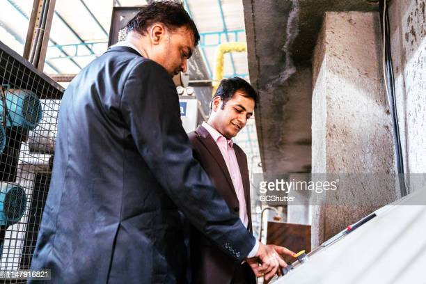 business owner powering on the new machinery at the factory - opening ceremony stock pictures, royalty-free photos & images