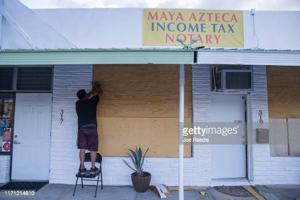 A business owner puts plywood over the windows of his office building as he prepares for the arrival of Hurricane Dorian on August 30 2019 in West...