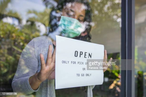 business owner putting open sign only for pick up delivery and take away food during covid 19 pandemic - open for business stock pictures, royalty-free photos & images