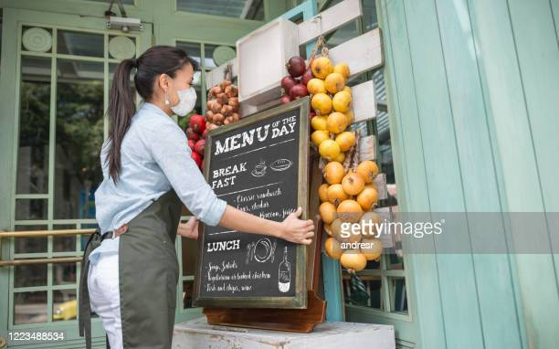 business owner reopening a restaurant while wearing a facemask - business owner stock pictures, royalty-free photos & images