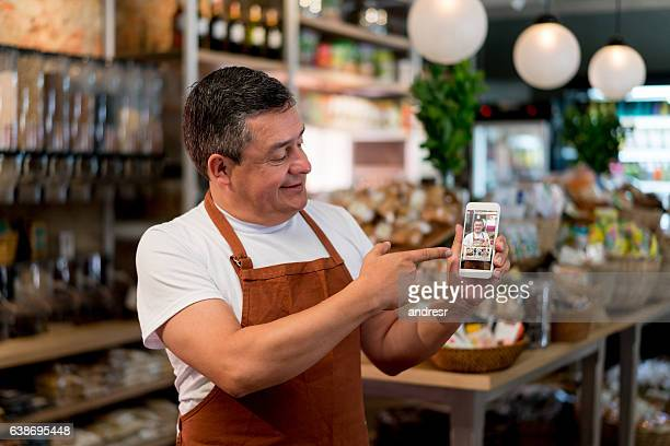 business owner selling food online at a grocery store - e commerce - fotografias e filmes do acervo
