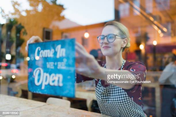 business owner setting up open sign in cafe window - business owner stock photos and pictures