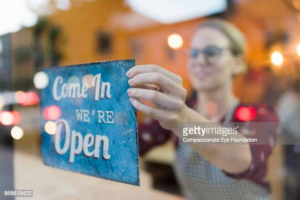 business owner setting up open sign in cafe window - cef do not delete stock pictures, royalty-free photos & images