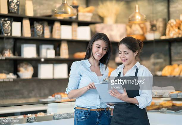 Business owner talking to worker at a bakery