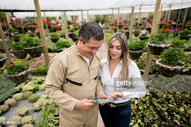 Business owner talking to worker at a greenhouse