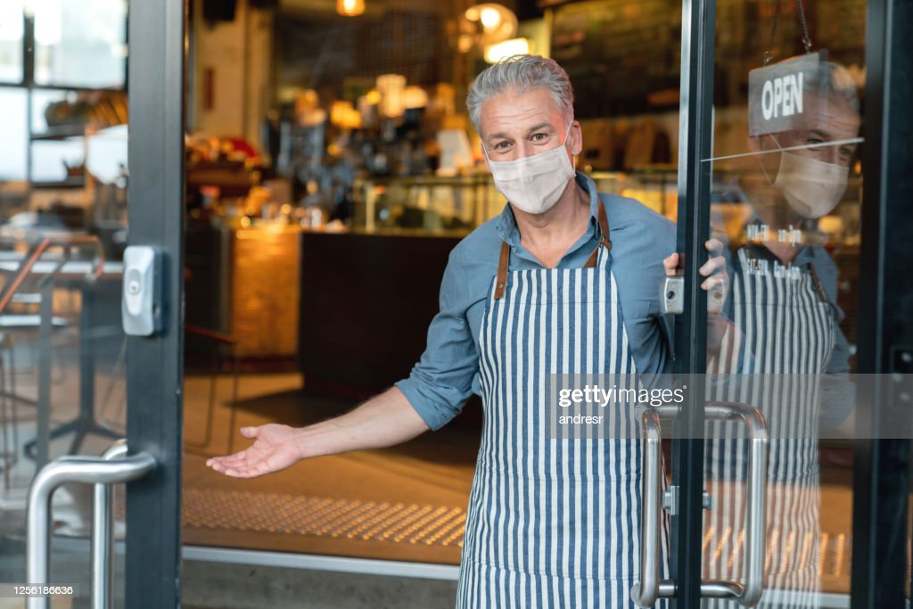 Business owner wearing a facemask and reopening his cafe after the quarantine : Stock Photo