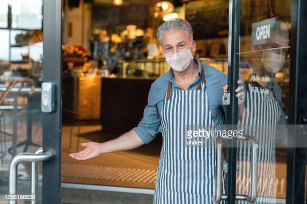 business owner wearing a facemask and reopening his cafe after the quarantine - opening event stock pictures, royalty-free photos & images