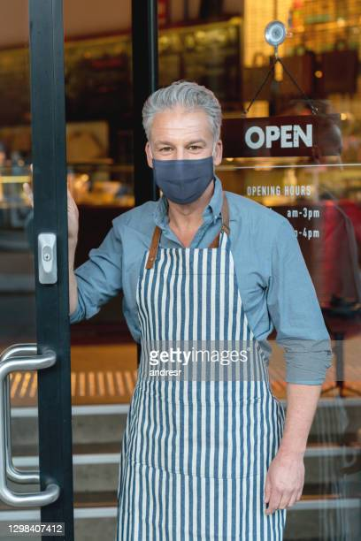 business owner wearing a facemask at a cafe while opening the door for clients during the pandemic - opening event stock pictures, royalty-free photos & images