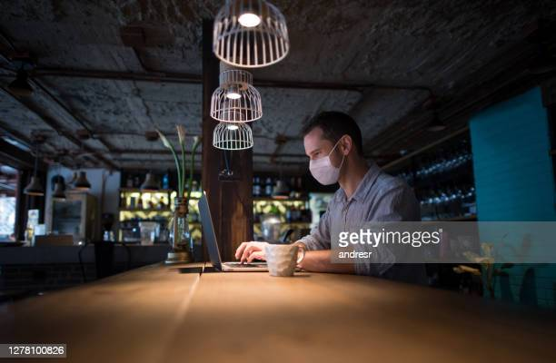 business owner wearing a facemask while bookkeeping at a restaurant - opening event stock pictures, royalty-free photos & images