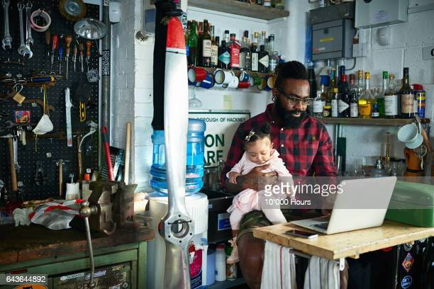 Business owner with baby daughter in motorcycle workshop.