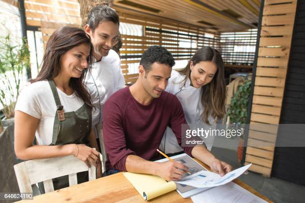 business owner with his staff at a restaurant - staff meeting stock pictures, royalty-free photos & images