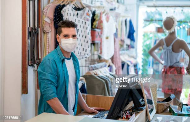 business owner working at a clothing store wearing a facemask - biosecurity stock pictures, royalty-free photos & images