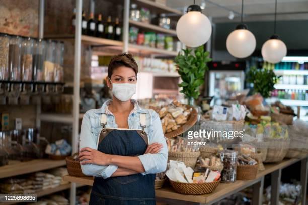 bedrijfseigenaar die bij een kruidenierswinkelopslag werkt die een facemask draagt - beschermend masker werkkleding stockfoto's en -beelden