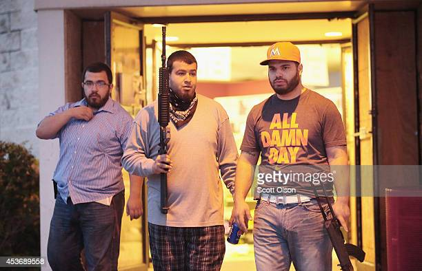Business owners carry assault weapons to protect their grocery store after another night of rioting and looting following protests over the shooting...