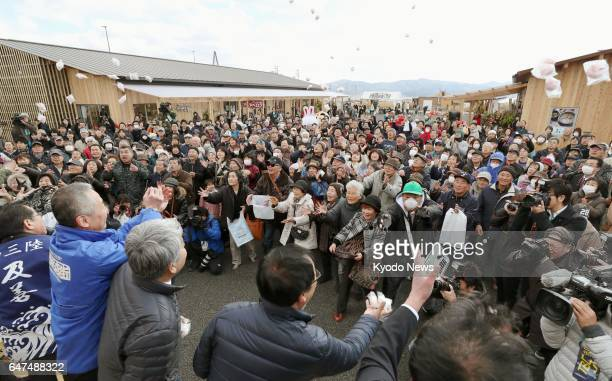 Business owners throw rice cakes to celebrate the opening of their stores on March 3 at a new commercial facility in Minamisanriku Miyagi Prefecture...