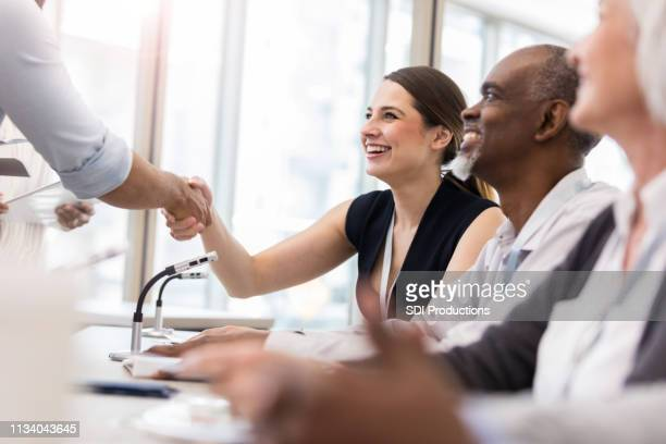 business panelist greets conference attendee - authors stock pictures, royalty-free photos & images