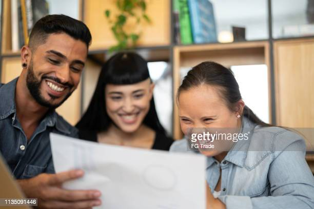 business partners (including special needs woman) discussing new project at modern startup office - differing abilities female business stock pictures, royalty-free photos & images