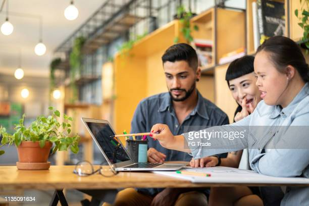 business partners (including special needs woman) discussing new project at modern startup office - community work stock pictures, royalty-free photos & images
