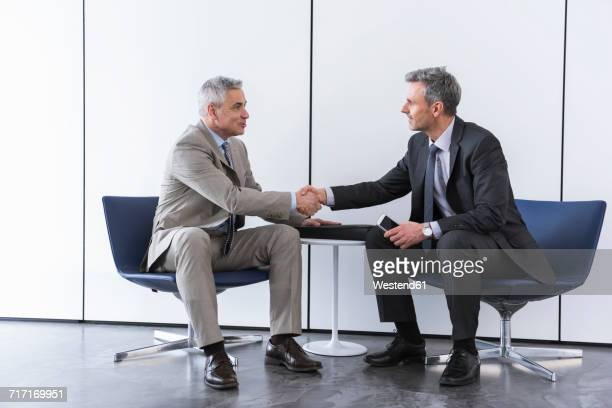business partners having a meeting, shaking hands - sitzen stock-fotos und bilder