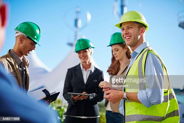 Business partners having a meeting with wind turbine engineer