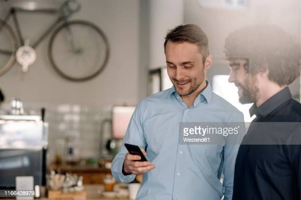 business partners in a coffee shop having a meeting, using smartphone - 創始者 ストックフォトと画像