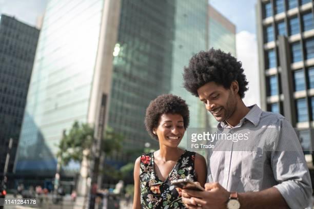 zakelijke partners lachen en het gebruik van mobiele op de stad - brazilië stockfoto's en -beelden