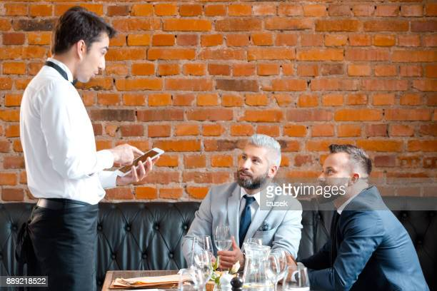 business partners making order at restaurant - demanding stock pictures, royalty-free photos & images