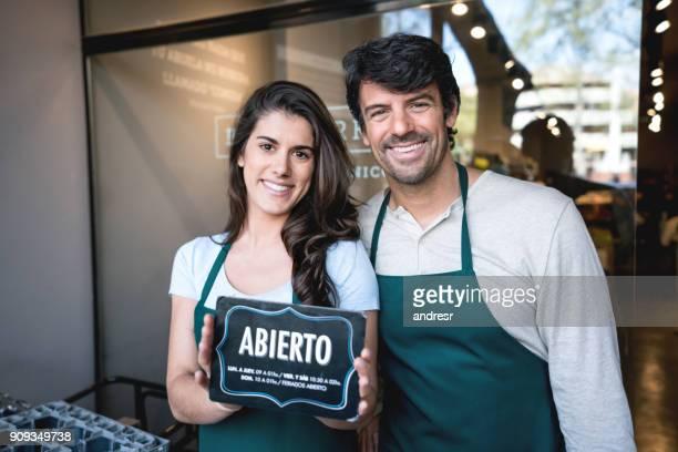 Partenaires commerciaux d'un standing de marché à l'entrée en regardant sourire caméra