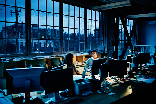 Business partners sitting at workstation in design office working late - gettyimageskorea