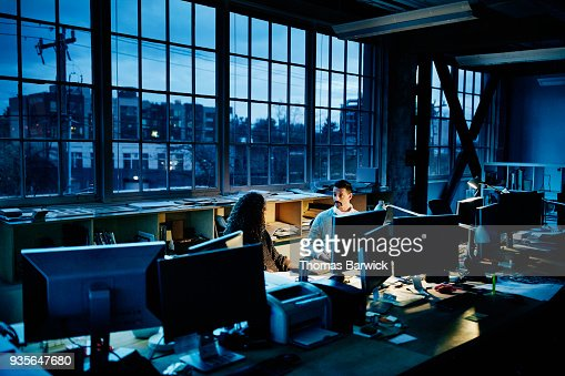 Business partners sitting at workstation in design office working late