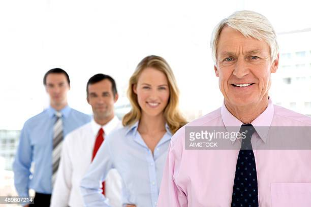 Business partners standing in row behind CEO