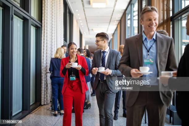 business partners talking during coffee break - unterhaltungsveranstaltung stock-fotos und bilder