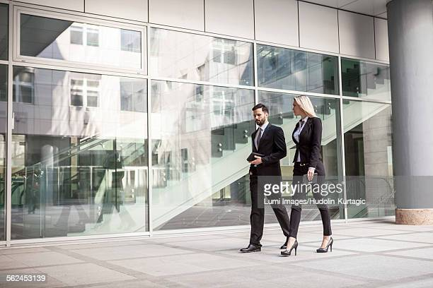 Business partners walking by office building