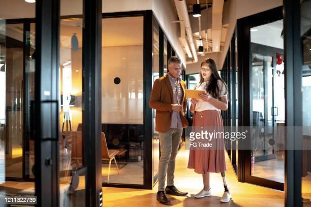 business partners walking using digital tablet at corridor - leanincollection stock pictures, royalty-free photos & images