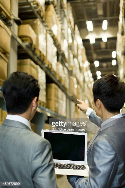 Business partners with laptop in logistic warehouse